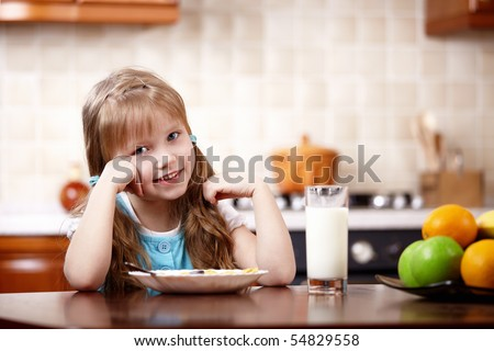 The little girl has breakfast on kitchen - stock photo