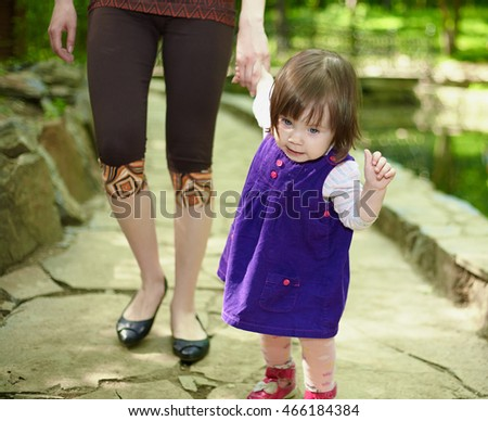 The little girl in a blue dress walking with her mother on the bridge