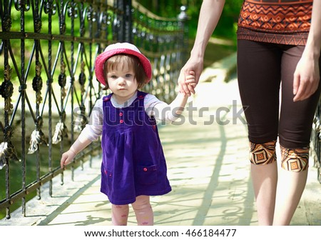 The little girl in a blue dress walking with her mother on the bridge.