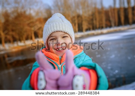 The little girl in a blue winter jacket lifts thumbs up and laughing, against the background of a winter frozen pond. - stock photo