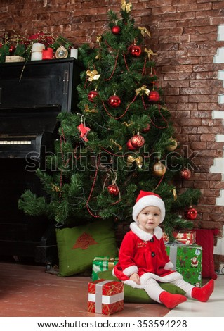 The little girl in a New Year's suit sitting under the Christmas tree, surrounded by Christmas gifts