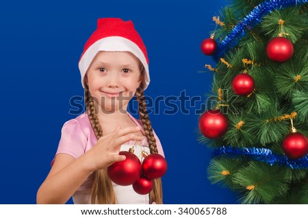 The little girl in a red cap holds New Year's toys in hand and smiles. Christmas. New year.