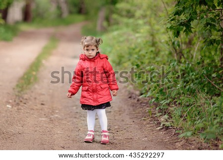 The little girl in a red jacket walks outdoor.