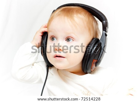 The little girl in ear-phones on white background - stock photo