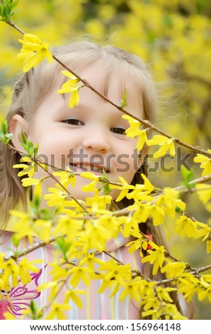 The little girl in flowers of quince - stock photo