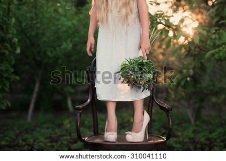 The little girl in high-heeled shoes large size in a white dress standing on a chair with a vintage bouquet in the hands of fashion, lifestyle, wedding