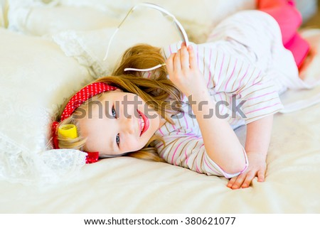 the little girl in pin up style in a striped terry dressing gown, in hair curlers and with a red bandage in peas poses on a bed with white sunglasses