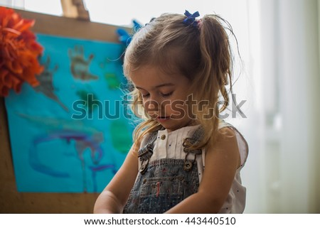the little girl in the painting process at the easel - stock photo