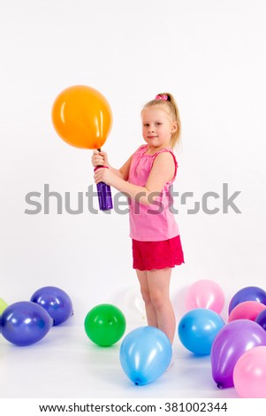 The little girl inflates a balloon in yellow color isolated on white
