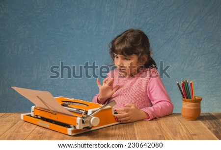 The little girl is being taught on a typewriter - stock photo
