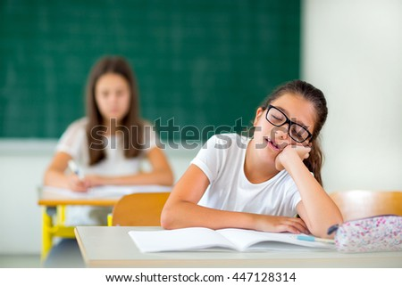 The little girl is bored in the classroom