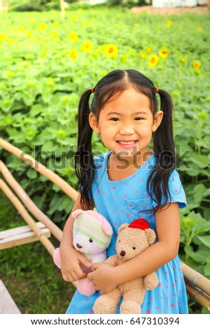The little girl is smiling with a teddy bear and is happy at the sunflower garden.