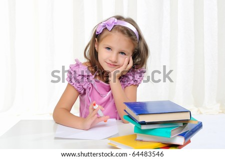 The little girl is studying literature. Reads a book while sitting at a white table.