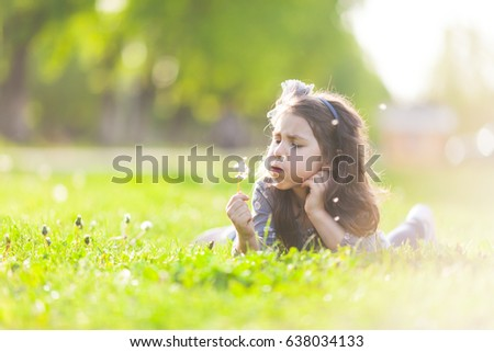 The little girl lays on a grass and blowing dandelion on the summer day