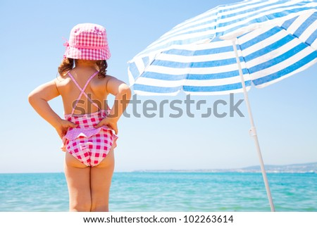 the little girl looks at the sea near a beach umbrella - stock photo