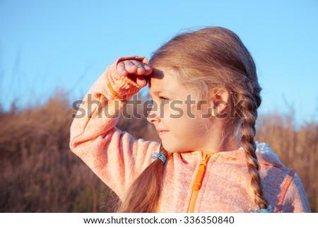 The little girl looks away, portrait on nature - stock photo