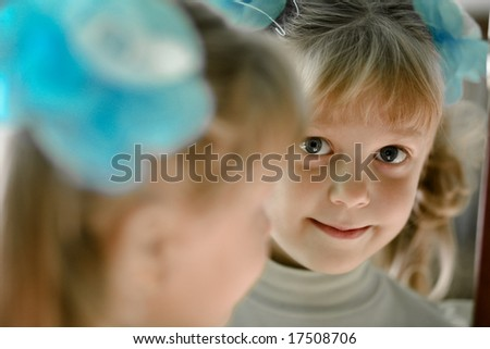 The little girl looks in the mirror
