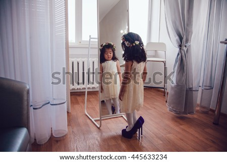 The little girl measures the mother's shoes in front of a mirror.