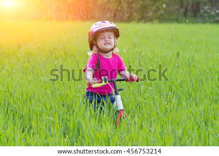 The little girl on a bike on the grass near the forest. - stock photo