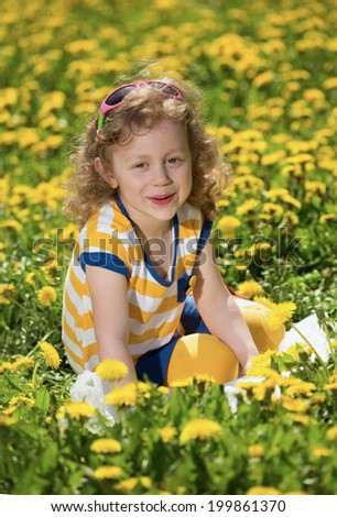 The little girl on a glade with dandelions