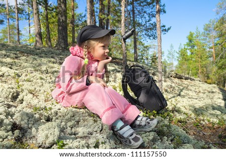 The little girl on a halt in the forest - stock photo