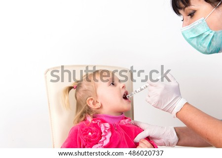 The little girl on reception at the doctor takes antipyretic, anti-flu, the child takes the medicine in the hospital