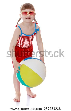The little girl on the beach with glasses holding a ball - isolated on white background - stock photo