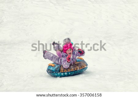 the little girl on the tubing rolls with slides - stock photo