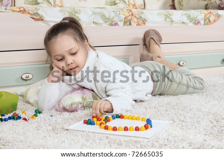 The little girl plays on a floor in developing children's game - stock photo