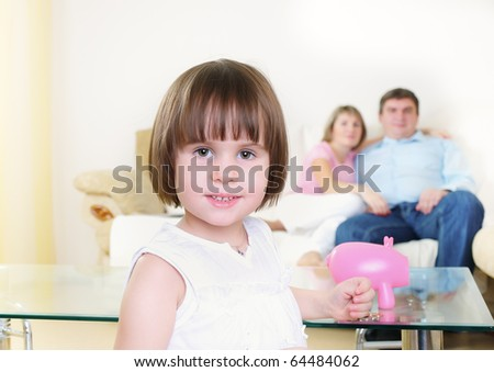 The little girl puts coins in his piggy bank pig - stock photo