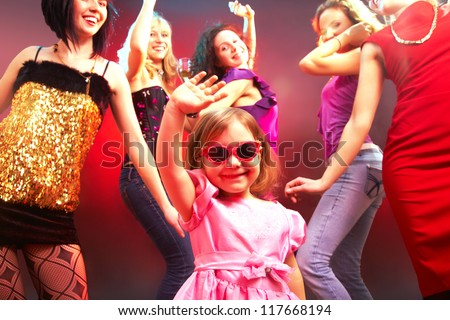 The little girl's dancing in a disco surrounded by big girls - stock photo