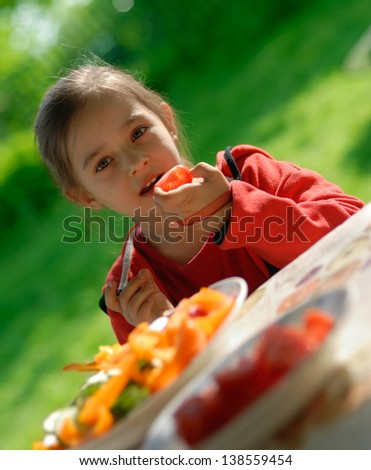 The little girl sits at a table on a verandah and eats fresh vegetables - stock photo
