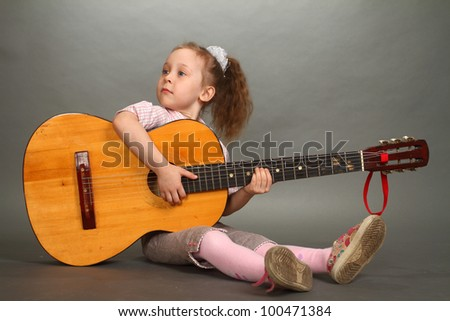 the little girl sits on a floor with a big guitar, a look not in a lens