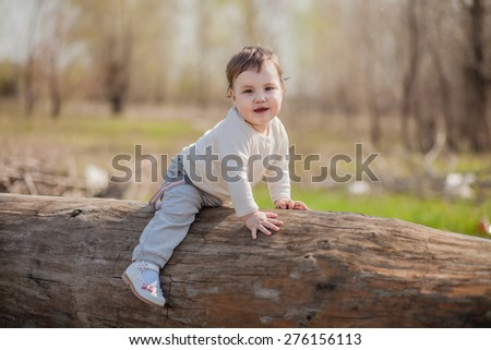the little girl sits on a log, selective focus