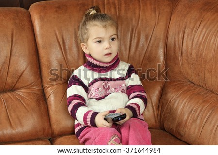 the little girl sits on a sofa with remote control in hands