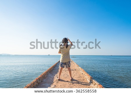 the little girl stay on the long way go into the sea with Clearly nice blue sea blue sky and yellow beach in summer of Thailand.