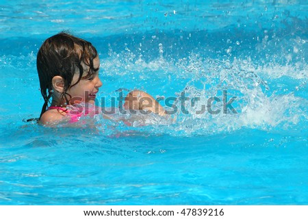 The little girl swimming in water pool - stock photo