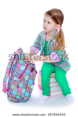 The little girl takes the book out of the school satchel , the girl sitting on stack of books-isolated on white background - stock photo