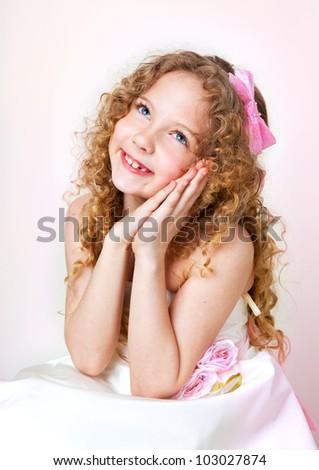 the little girl thinks and dreams. she looks up and smile - stock photo