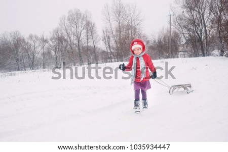 The little girl walks in the winter in the outdoors. The girl keeps snow in mittens