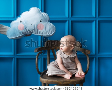 The little girl was frightened of a cloud. The father holds over the head the girl a pillow in the form of a cloud. - stock photo
