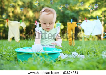 The little girl washes clothes in a small green basin near the rope with drying clothes - stock photo