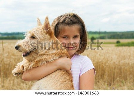 the little girl with a dog the Scottish terrier on hands in the field - stock photo