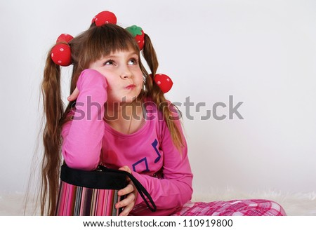 The little girl with a pink box in hands dreams of a gift - stock photo