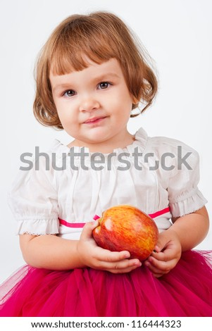 The little girl with an apple, on a gray background