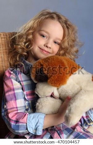 The little girl with blond curly hair playing with a toy puppy. Portrait of the child with the soft toy.