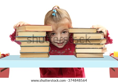 the little girl with books at a table. isolated on a white background