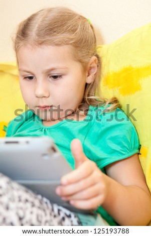 The little girl with enthusiasm playing with the tablet computer in the hands - stock photo