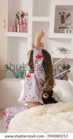 The little girl woke up in a comfortable bedroom and stretches on the bed