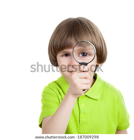 the little kid looks through a magnifying glass - stock photo